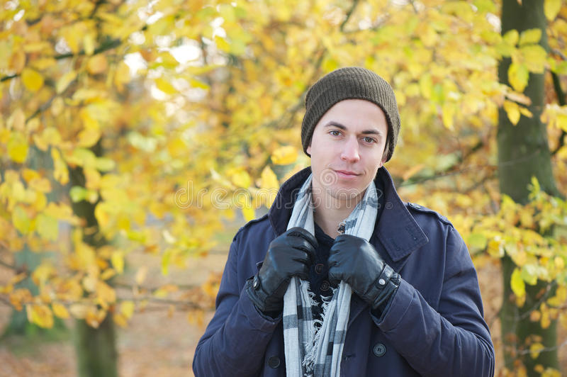 Handsome young man standing outdoors with jacket hat scarf and gloves. Close up portrait of a handsome young man standing outdoors with jacket hat scarf and stock images
