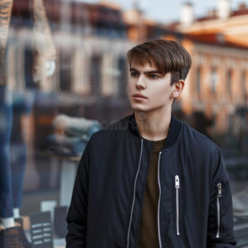 Handsome young man in stylish black jacket shopping near stock photo