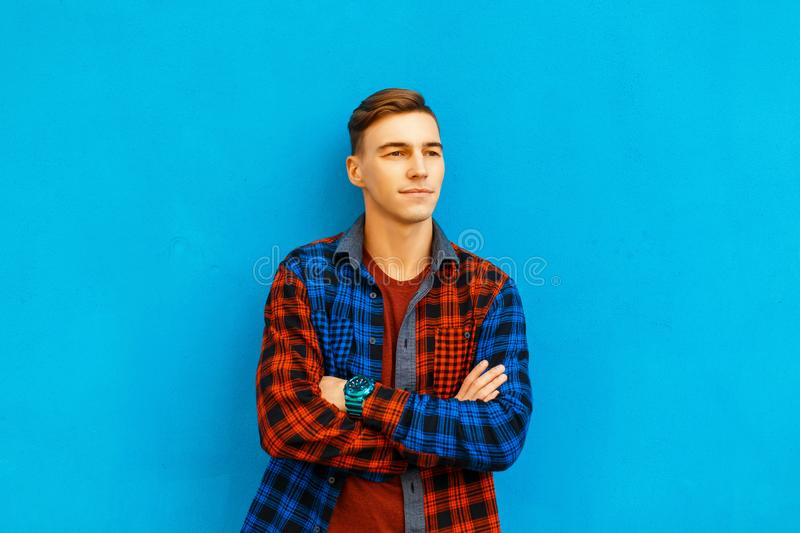 Handsome young man in stylish clothes poses near a blue wall. stock image