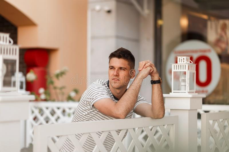 Handsome young man with a stylish hairstyle in a trendy striped t-shirt is standing near a vintage wooden fence in a street cafe. royalty free stock photos