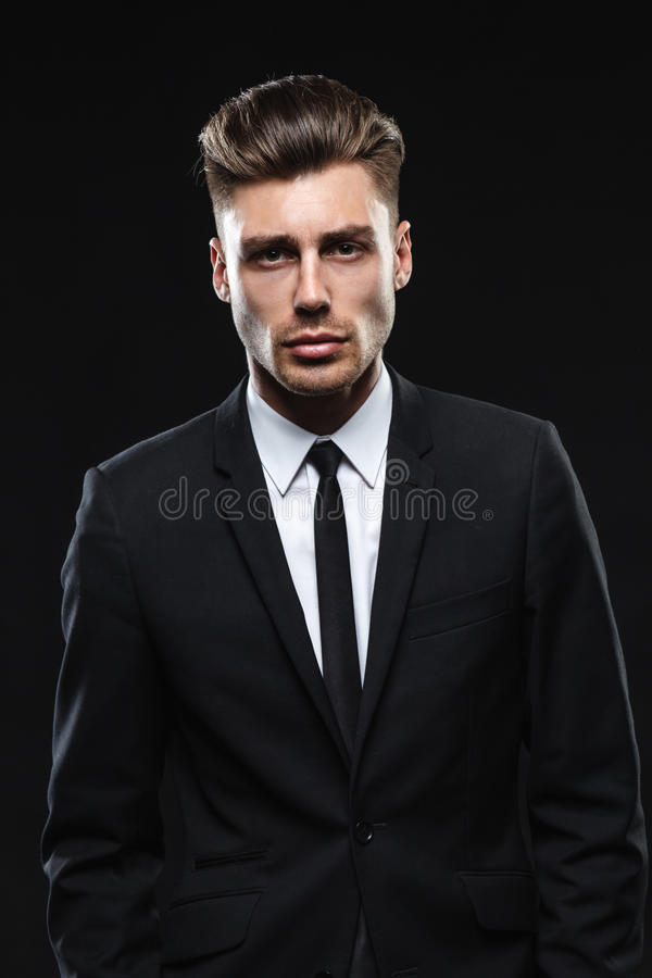 Handsome young man in suit on dark background. Brunette handsome man in a suit on a dark background royalty free stock photo