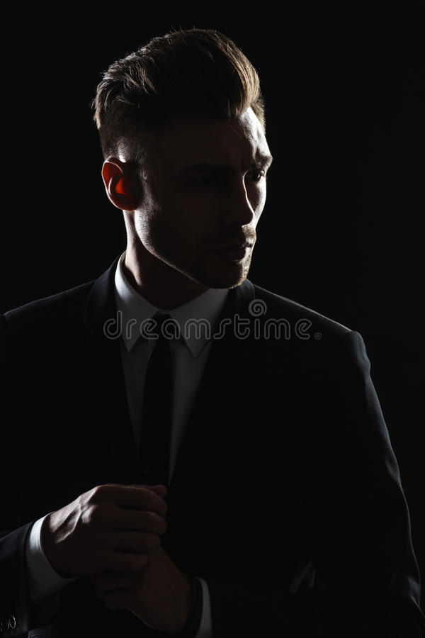 Handsome young man in suit on dark background stock photo