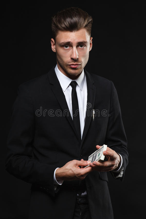 Handsome young man in suit on dark background with. Brunette handsome man in a suit on a dark background with money stock photo