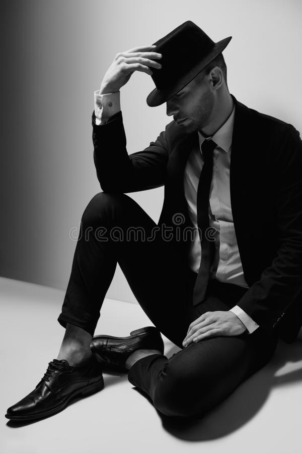 Handsome young man in suit and hat posing sitting on floor stock photography