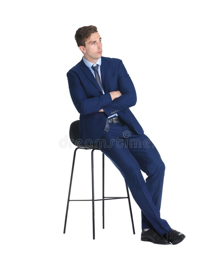 Young man in suit sitting on chair against white background stock image