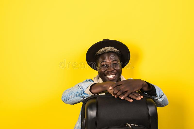 Handsome young african man in summer outfit holding suitcase and looking away isolated on yellow background royalty free stock photo