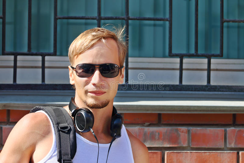 Handsome young man in sunglasses and headphones stock image