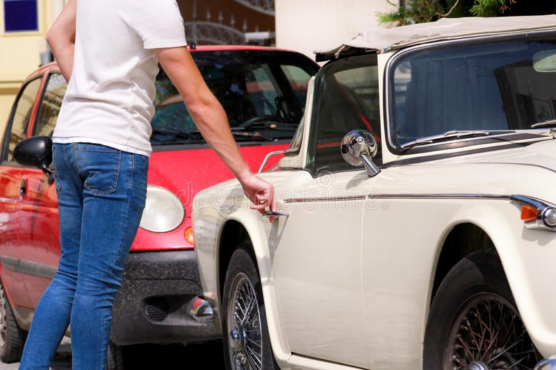 Handsome young man in sunglasses standing in urban city street next to an old retro car. A guy opening and entering old timer car. stock photo