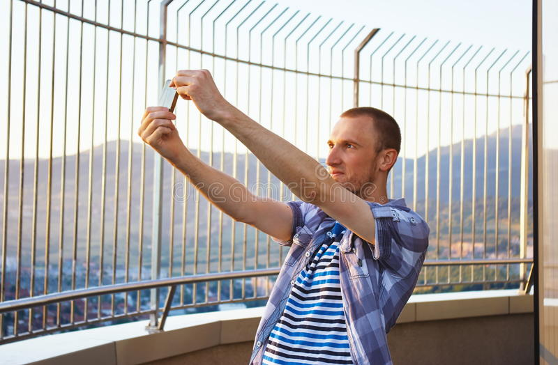 Handsome young man taking selfie camera with smartpone camera royalty free stock images