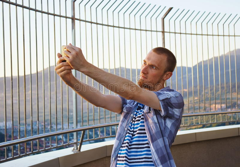 Handsome young man taking selfie camera with smartpone camera royalty free stock photo