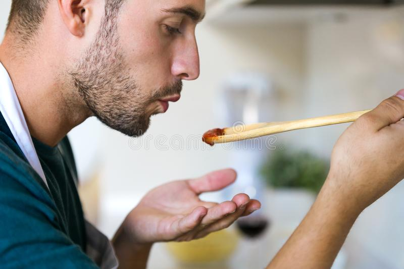 Handsome young man tasting the fried with wooden spoon in the kitchen at home. stock photography