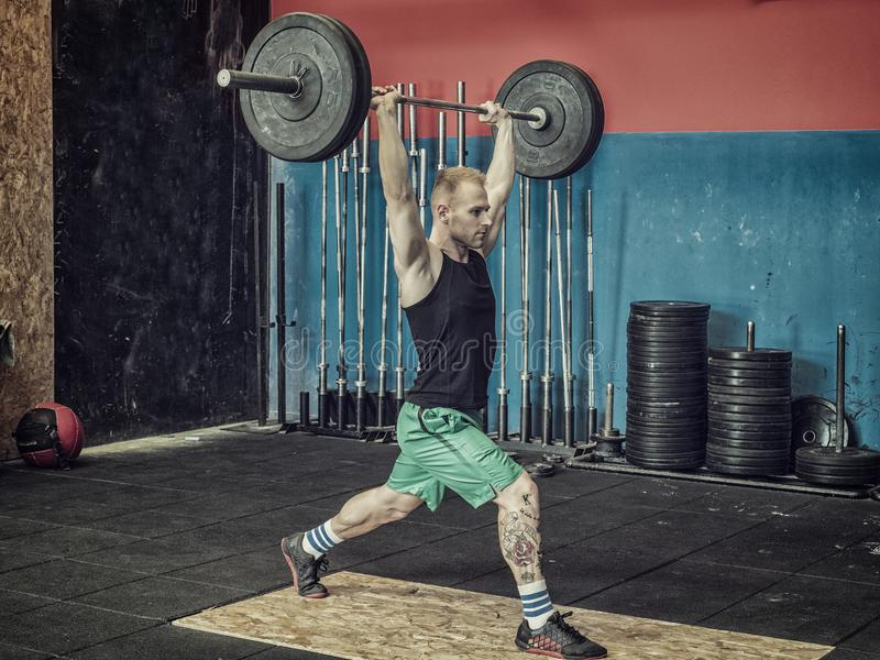 Young man training legs in gym. Handsome young man training legs practising weightlifting specialty with barbell, in a gym royalty free stock photos