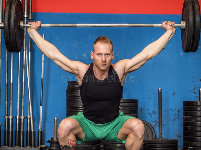 Young man training legs in gym. Handsome young man training legs practising weightlifting specialty with barbell, in a gym royalty free stock images