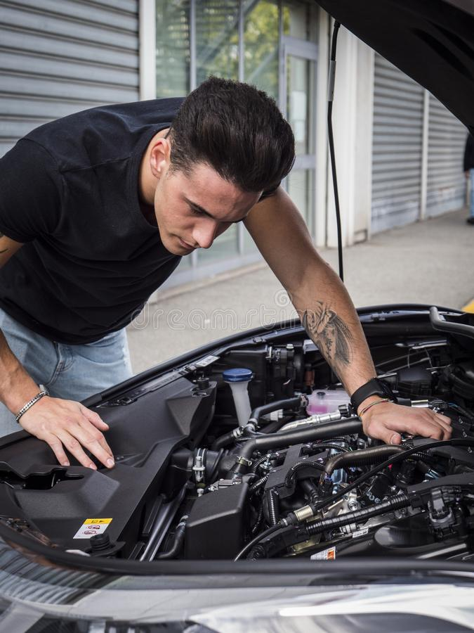 Handsome young man trying to repair a car engine. Looking inside open bonnet royalty free stock photos