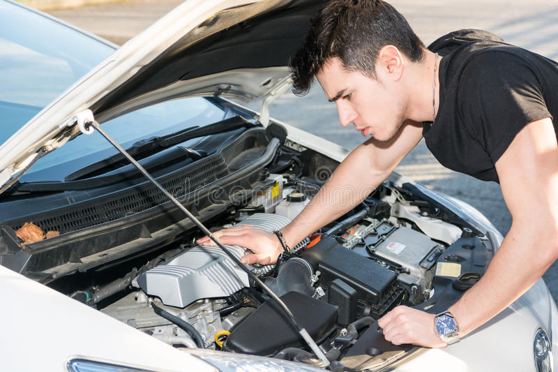 Handsome young man trying to repair a car engine. Looking inside open bonnet royalty free stock photo