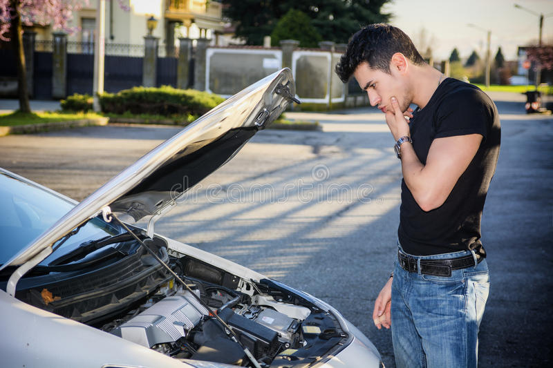 Handsome young man trying to repair a car engine. Looking inside open bonnet royalty free stock image