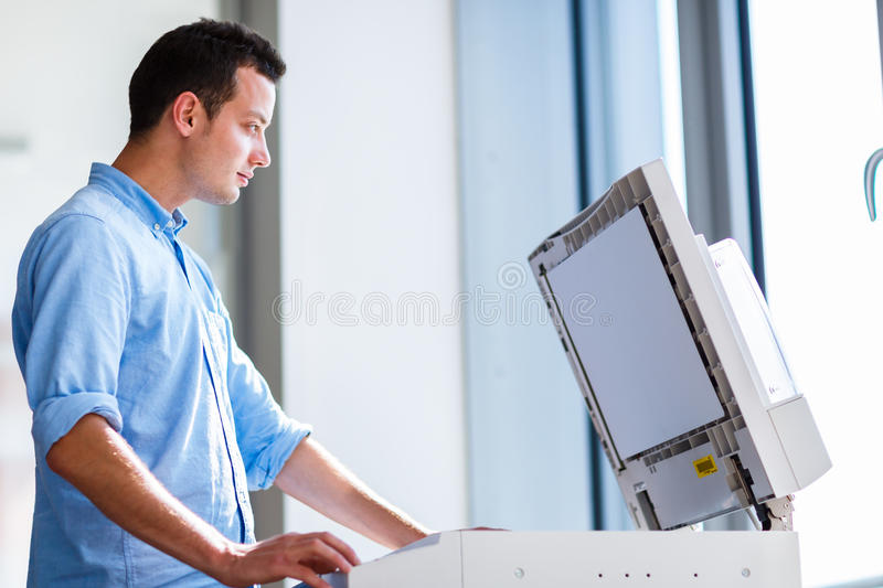 Handsome  young man using a copy machine