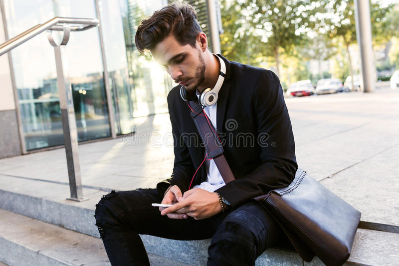 Handsome young man using his mobile phone in the street. royalty free stock photos