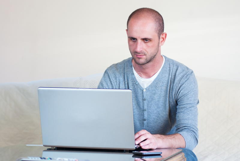 Handsome young man using laptop computer stock photography