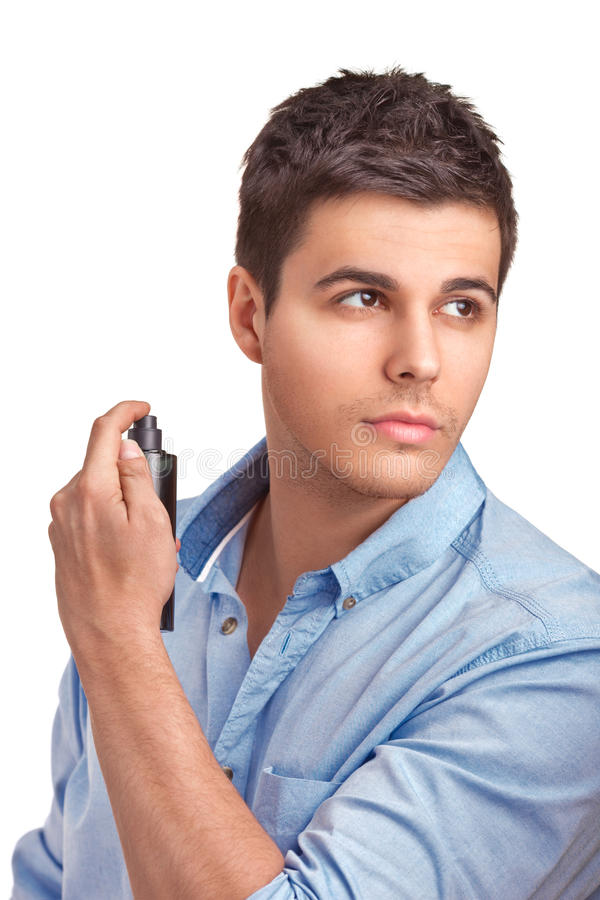 Handsome young man using perfume stock photography