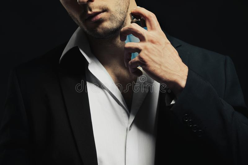 Handsome young man using perfume stock images