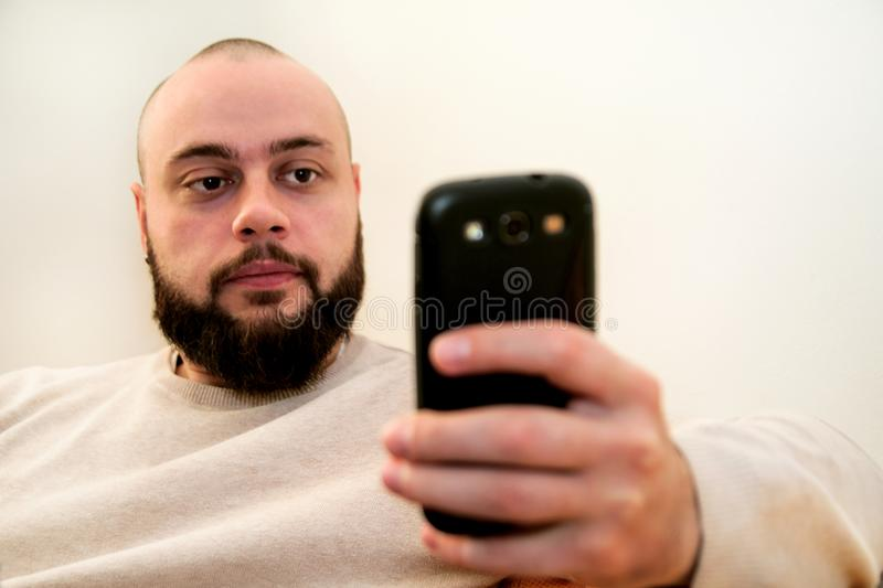 Young man using on smart phone at home office stock image