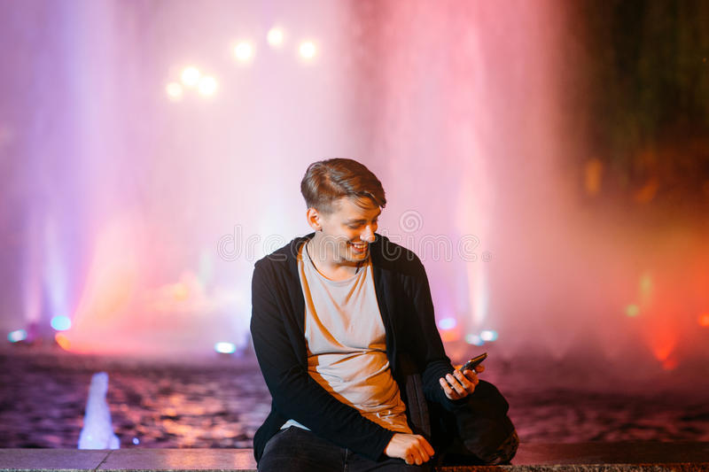 Handsome young man using smartphone in city royalty free stock image