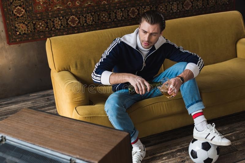 Handsome young man in vintage clothes with ball watching soccer on old tv and pouring beer. Into mug stock photography