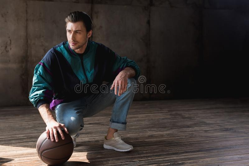 Handsome young man in vintage windcheater with basketball ball sitting squats. On wooden floor royalty free stock image