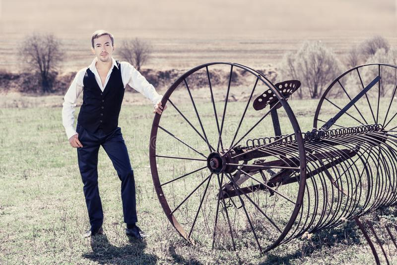 A handsome young man in a waistcoat, black trousers and a white shirt is standing next to a haymaking machine in the field. He loo royalty free stock images