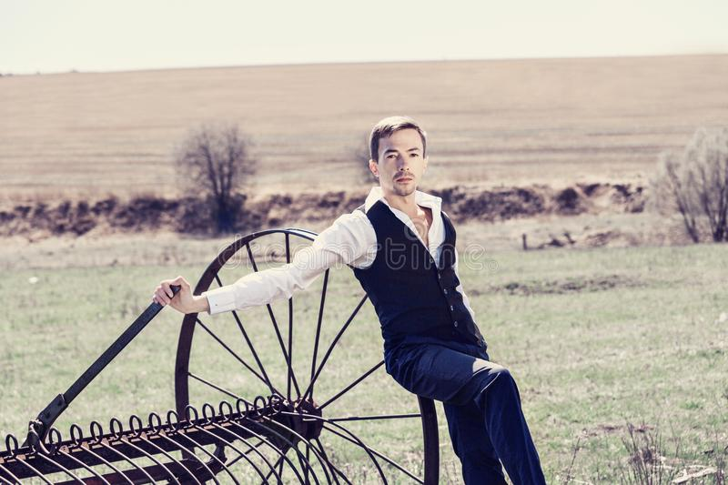 A handsome young man in a waistcoat,. Black trousers and a white shirtbased on a haymaking machine in the field. Looks at the camera stock photography
