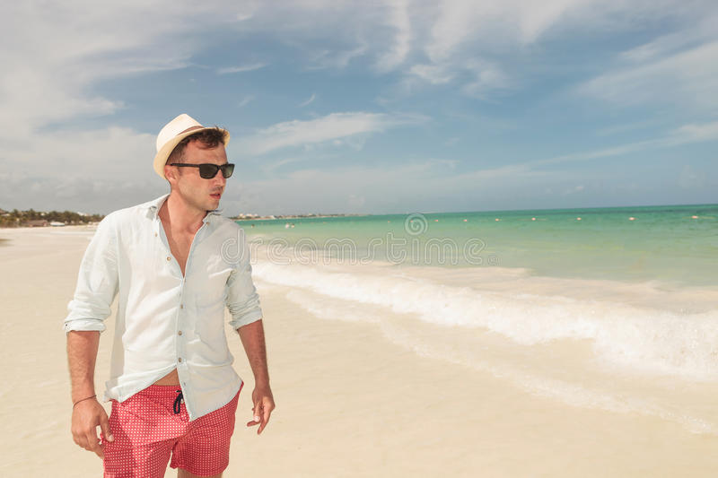 Handsome young man walking on the beach, royalty free stock image