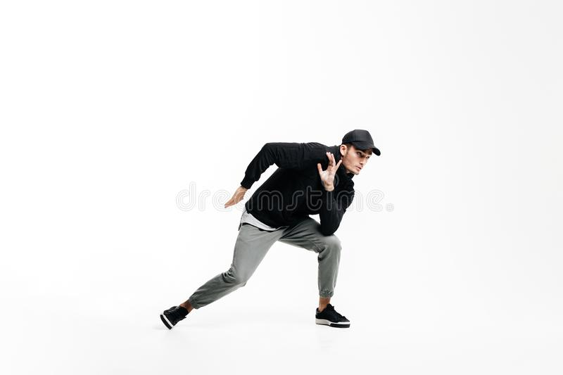 Handsome young man wearing a black sweatshirt, gray pants and a cap dancing street dances on a white background royalty free stock images