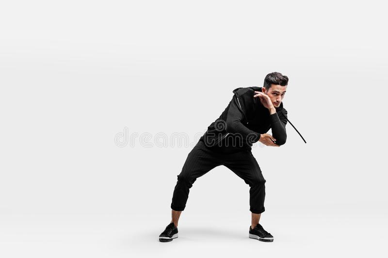 Handsome young man wearing a black sweatshirt and black pants is dancing breakdance royalty free stock photography