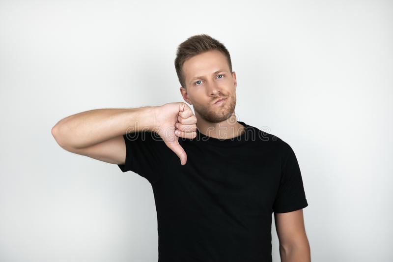 Handsome young man wearing black t-shirt showing dislike with negative expression isolated white background royalty free stock photos