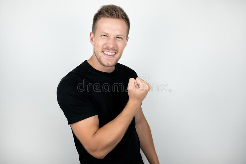 Handsome young man wearing black t-shirt showing winner success yes sign positive smiling looks happy isolated white royalty free stock photo