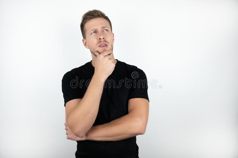 Handsome young man wearing black t-shirt touching his face with one hand looks pensive isolated white background stock photos