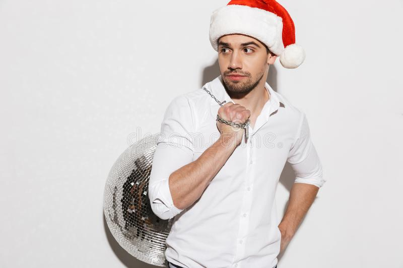 Handsome young man wearing santa claus hat royalty free stock photo