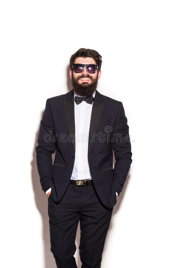 Handsome young man wearing suit and glasses keeping hands in pockets and looking at camera stock image