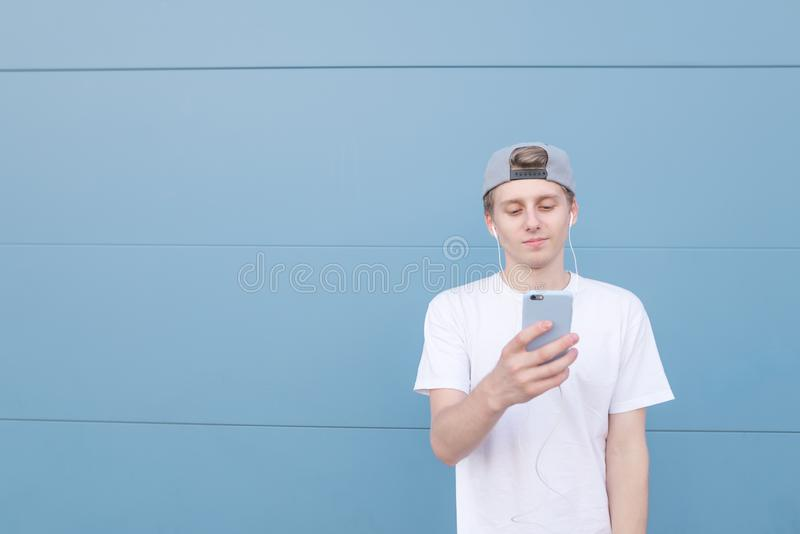 Handsome young man wearing a white T-shirt and cap is listening to music in the headphones stock photo