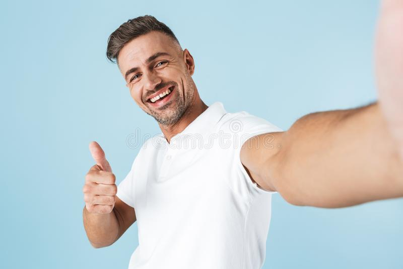 Handsome young man wearing white t-shirt standing stock photo