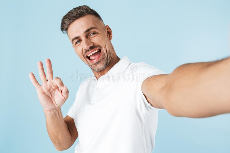 Handsome young man wearing white t-shirt standing royalty free stock photography