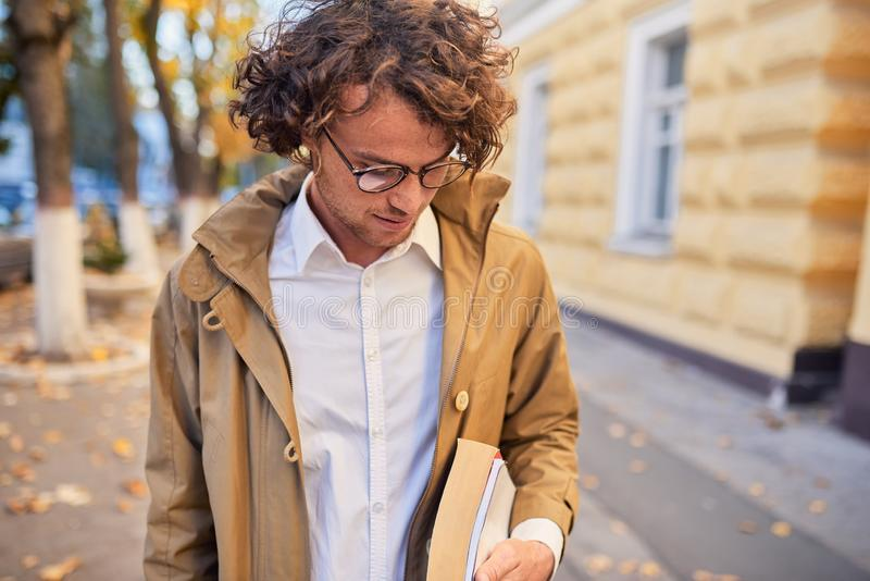 Handsome young man wears spectacles with books outdoors. College male student carrying books in college campus in autumn street. Background. Smiling cheerful royalty free stock image