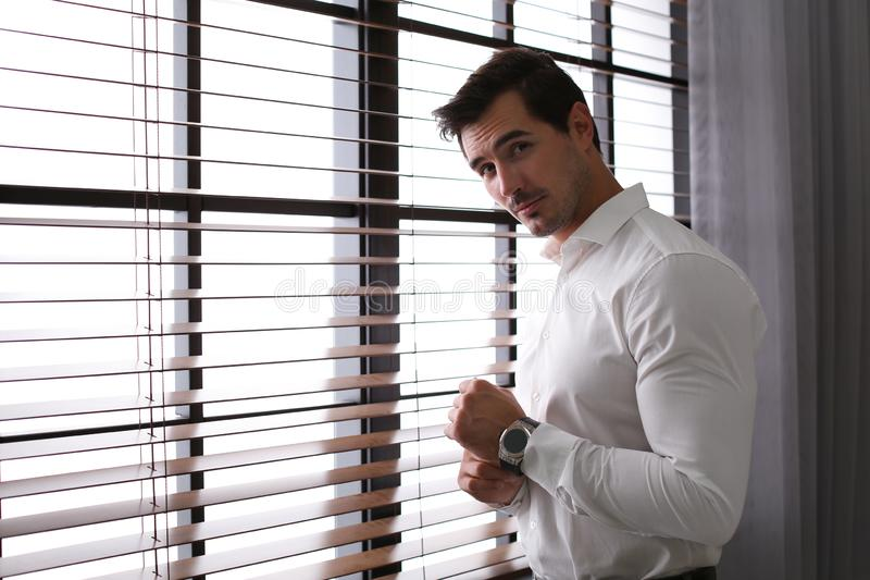 Handsome young man in white shirt standing  window indoors stock photos