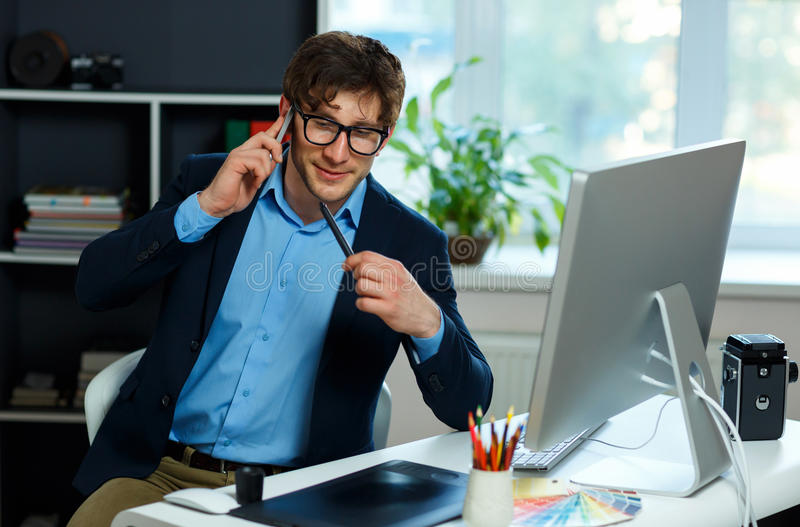 Handsome young man working from home office and using smartphone royalty free stock photography