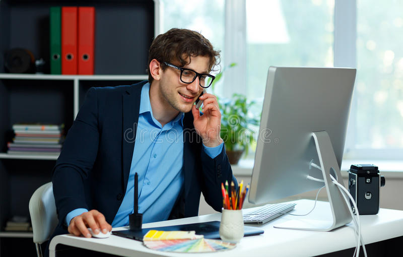 Handsome young man working from home office and using smartphone royalty free stock image