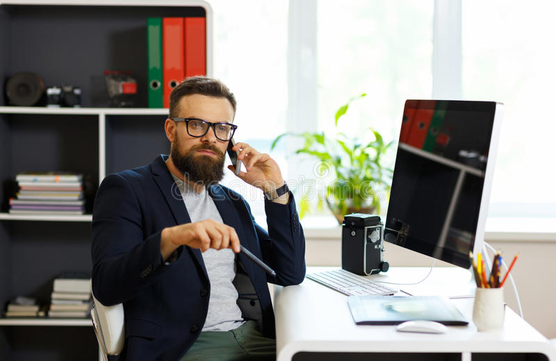 Handsome young man working from home office and using smartphone royalty free stock photos