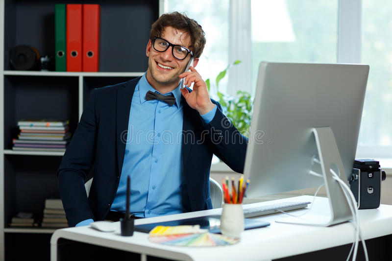 Handsome young man working from home office and using smartphone stock image