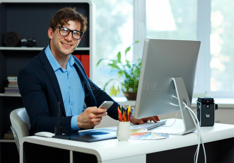 Handsome young man working from home office and using smartphone royalty free stock images