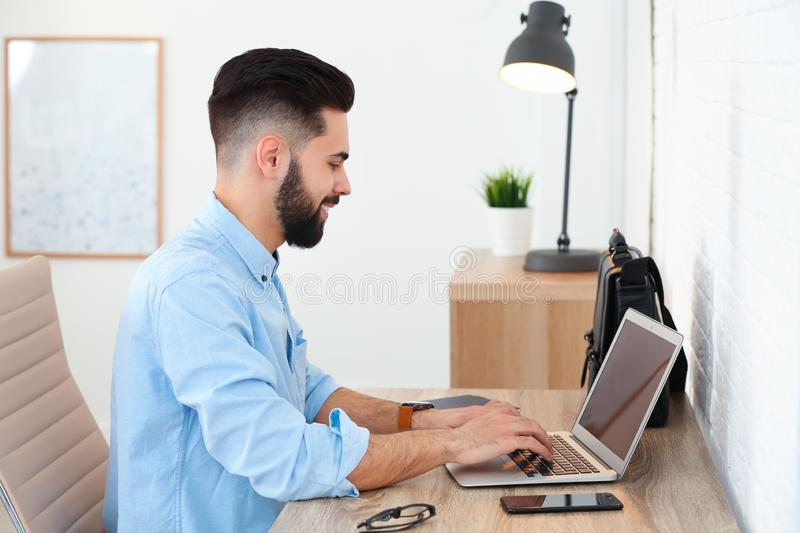 Handsome young man working with laptop at table in home stock photography